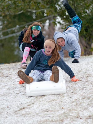 In this file photo from January, Brooke Gaston, left, and Brantley Haferkamp, right, sends Carlisle Gaston, center down an icy hill in Bayview Park in Pensacola after a winter storm blanketed the city in ice.