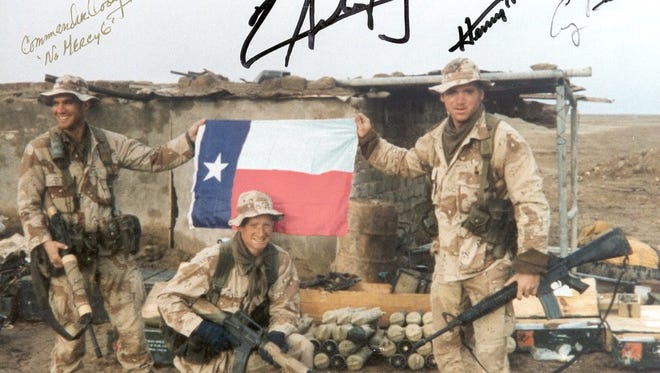 Team 4: John Carter, Clinton Dorris, Derrick Hart (all Texas boys) along the pipeline near Al Khidr at the Euphrates River after link-up. That Texas flag saved our lives when a 101st Airborne gunship trained its guns on us to fire. Clinton pulled the flag out of his ruck and rolled over and placed the flag on his chest. The pilot's eyes got so big that we could see them from the ground. We are smiling because we had just eaten fresh-cooked chicken stew that the Iraqi soldiers had left when they heard the 101st birds flying in. Taken in front of captured Iraqi weapons cache. Signed by President George Bush, Gen. Hugh Shelton, Col. Richard Cody, and Gen. Norman Schwarzkoph. Team 4, Long Range Surveillance Detachment, 2/17th Cavalry, 101st Airborne Division.