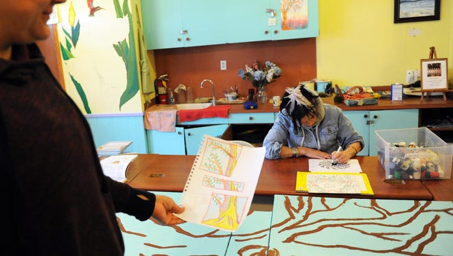 Rana Ghana, left, holds a sketch of the triptych she's working on, while Judy Wilson paints in the chnurch's art room.