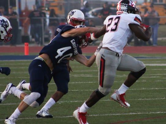 Many High School running back AJ Carter(23) stiff arms