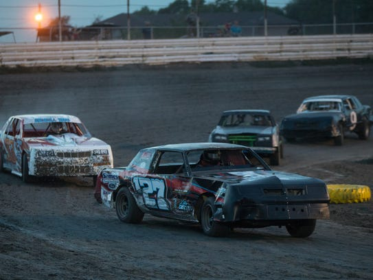Cars race around a dirt track at the South Texas Speedway
