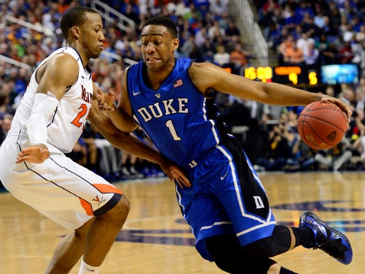 Duke Blue Devils forward Jabari Parker (1) moves the ball up the court against Virginia Cavaliers forward Akil Mitchell (25) in the championship game of the ACC college basketball tournament at Greensboro Coliseum.