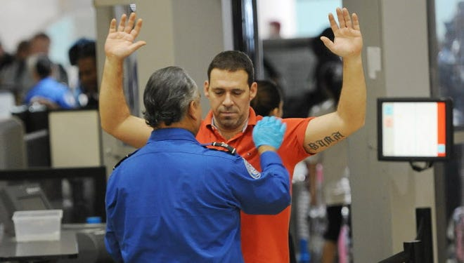 An air traveler is patted down after passing through a full-body scanner at the Transportation Security Administration checkpoint at  Los Angeles International Airport on February 20, 2014.
