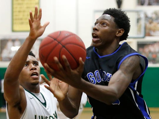 Godby's Quan Jackson lays the ball up past Lincoln's Kyle Kincey during their game at Lincoln High School on Thursday.