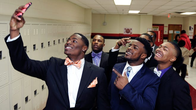 Pearl-Cohn football players Koreyon Jordan, left,  Ke'Shawn Vaughn and Mario Gordon pose for a selfies in the school hallway before going to their signing day ceremony on Feb. 4, 2015.