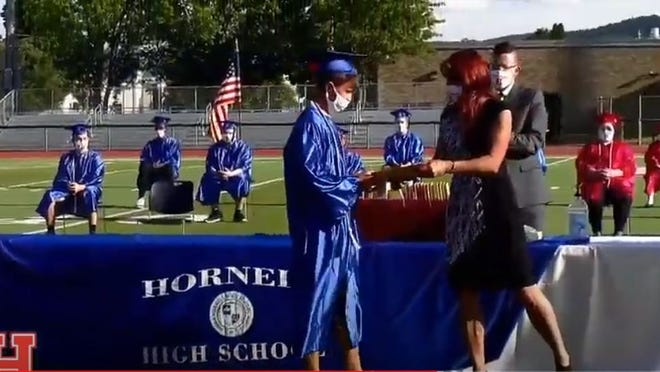 Hornell High School Class of 2020 graduate Chase Freeland accepts his diploma from board of education president Kerry Davis at Friday's commencement ceremony.