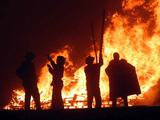 Revelers stand near the fires during the first of the