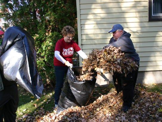 Christine and Dana Duncan help rake a yard on 3rd Street