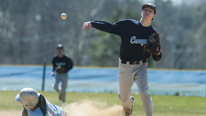 MMU's James Gaboriault (20) turns the double play as South Burlington's Jake Mann (16) slides into second base during the high school baseball game between the Mount Mansfield Cougars and the South Burlington Rebels at South Burlington High School on Saturday.