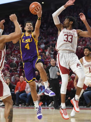 LSU guard Skylar Mays (4) tries to drive past Arkansas defender Jimmy Whitt Jr.  (33) during the second half of an NCAA college basketball game Wednesday, March 4, 2020, in Fayetteville, Ark. (AP Photo/Michael Woods)
