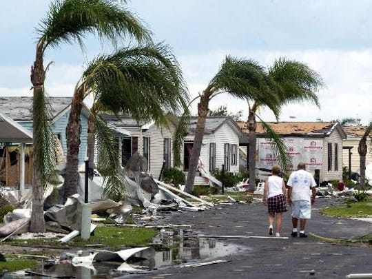 A couple walks past downed palm trees and destroyed mobile homes Saturday, Aug. 14, 2004, in a community in South Punta Gorda