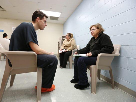 Rosa Ramirez surveys inmate David Rumplik at the Marion