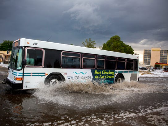 A bus travels through a flooded S. Main St. after a