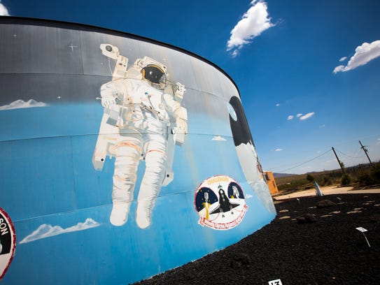 A water tank is painted with scenes from NASA's history