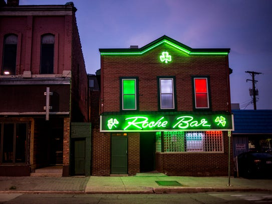 Neon lights illuminate the front of the Roche Bar in