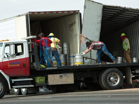 Workers unload kegs of beer from a crashed RM Trucking