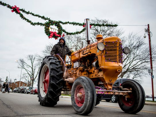 An antique tractor decorated with lights drives down