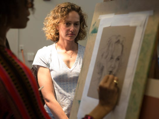 An artist draws the face of her subject during  'Portraits