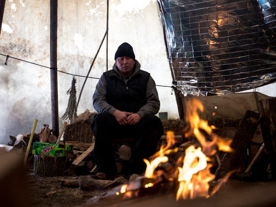 "Joey Powless watches the ""sacred fire"" in Oneida, Wis.,"