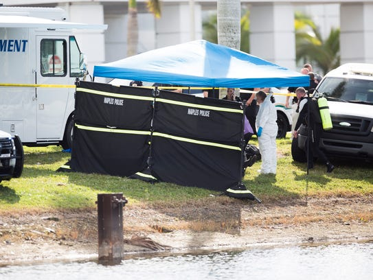 Naples Fire-Rescue and police officials investigate the scene where a body was found floating in a pond on Naples Municipal Airport property early Monday, Jan. 29, 2018.