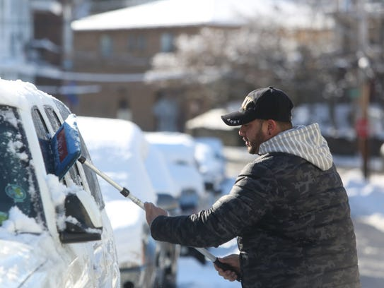 Roberto Gomez clears his car in Tarrytown Sunday morning.