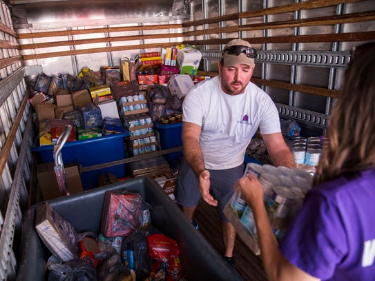 Taylor Grove helps load the St. Matthew's House donation