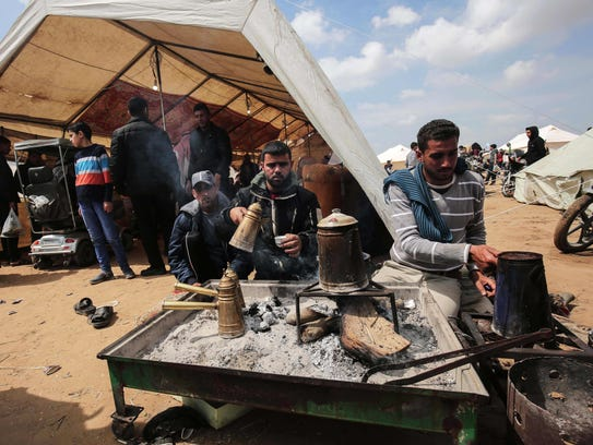 Palestinians protesters make traditional coffee as