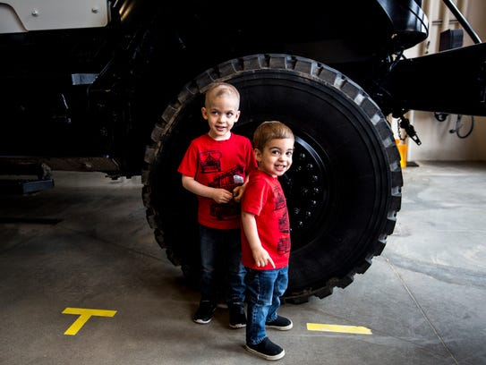Lincoln Schrock and his brother Bridger stand next to the tire of a police vehicle at the Marshfield Fire and Rescue Station in Marshfield, Wis., May 3, 2018.