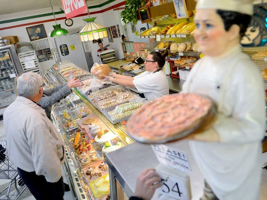Beverly Willett, right, helps a customer with a bread order at Roma Bakery Wednesday, Nov. 23, 2016 in Lansing.