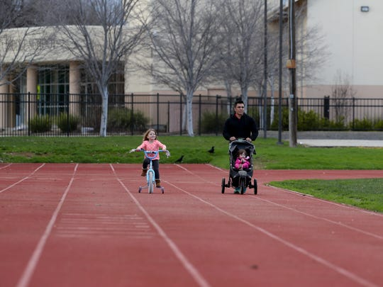 Vincent Alderman pushes his daughter Camille, 20 months, while daughter Savannah, 4, rides her bike Saturday Feb. 18 at Sequoia Middle School in Redding.