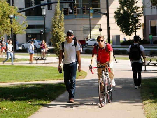 A cyclist navigates between pedestrians on a sidewalk