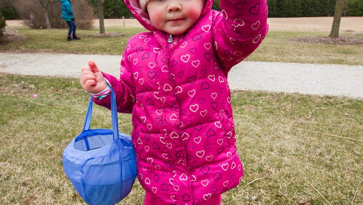 Two-year-old Emily Wojciga of Sussex holds up a candy filled egg she found during the annual Town of Lisbon Easter Egg hunt and festivities at Lisbon Community Park on Saturday, March 19, 2015.