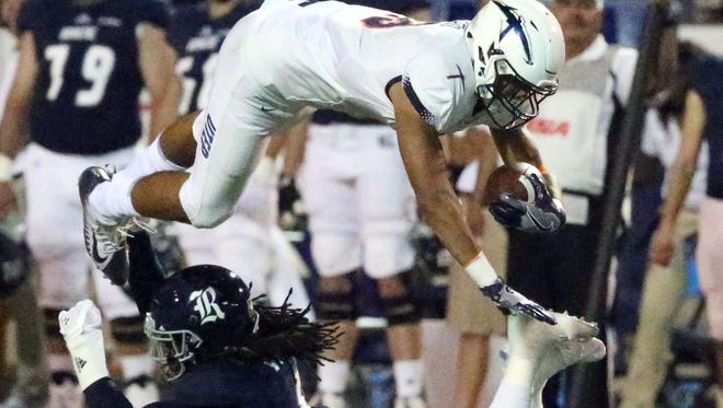 UTEP tight end David Lucero, 18, flies over Destri White of Rice for yardage late in the third quarter Saturday night in the Sun Bowl.