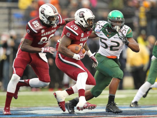 Dec 27, 2014; Shreveport, LA, USA; South Carolina Gamecocks tailback Mike Davis (28) rushes during the first half as Miami Hurricanes linebacker Denzel Perryman (52) closes in during the first quarter in the 2014 Independence Bowl at Independence Stadium. Mandatory Credit: Nelson Chenault-USA TODAY Sports