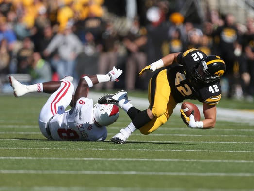 Iowa fullback Macon Plewa is upended by Indiana's Tegray