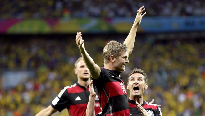 Germany's Toni Kroos celebrates with Miroslav Klose after scoring his side's third goal during the World Cup semifinal soccer match between Brazil and Germany at the Mineirao Stadium in Belo Horizonte, Brazil, Tuesday, July 8, 2014.