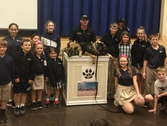 Phil Ryan, Raven's handler (center) with Finn (dog