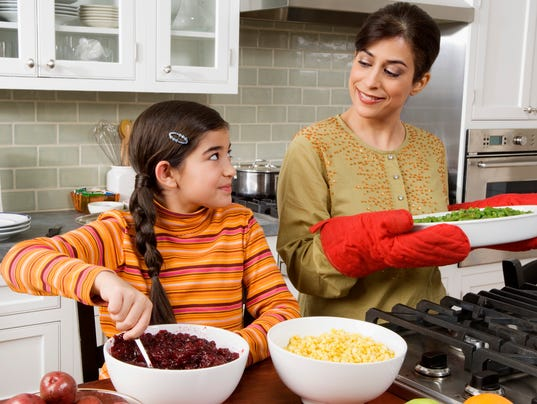 Mother and daughter cooking Thanksgiving meal in kitchen