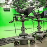 Cameras wait in front of empty green screens for future filming at WIPB studios.