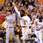 The Pirates' Josh Harrison heads home with the winning run after hitting a triple and then scoring on Scooter Gennett's throwing error in the ninth inning on Tuesday.