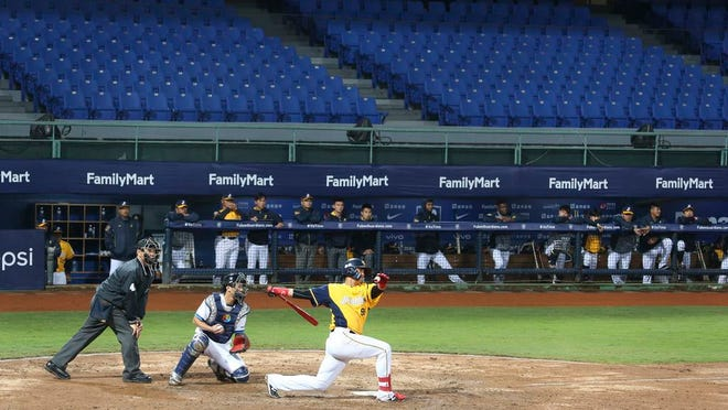 Players of Chinese Professional Baseball League play baseball with no audience at Xinzhuang Baseball Stadium in New Taipei City, Taiwan, Friday, April 24, 2020. Taiwan's five-team Chinese Professional Baseball League is barring spectators over concerns they would spread the deadly coronavirus, meaning games are played with plastic seats void of fans.