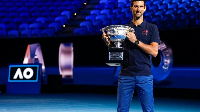 Defending men's singles champion Serbia's Novak Djokovic holds the Norman Brookes Challenge Cup during the official draw ceremony on Margaret Court Arena ahead of the Australian Open tennis championship in Melbourne, Australia, Thursday, Jan. 16, 2020.