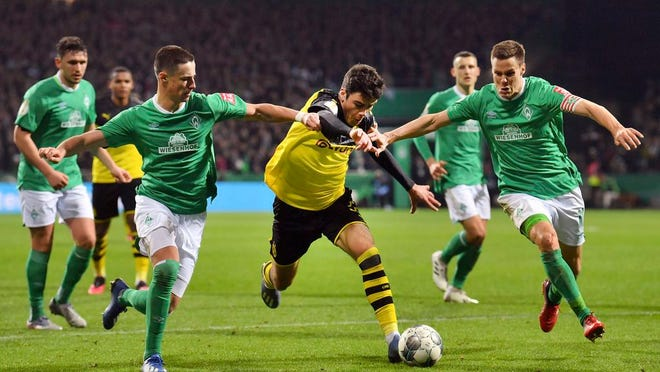 Dortmund's Giovanni Reyna, middle, moves the ball against Werder's Marco Friedl, left, and Niklas Moisander, right, during a soccer game, Tuesday, Feb. 4, 2020 in Bremen, Germany.