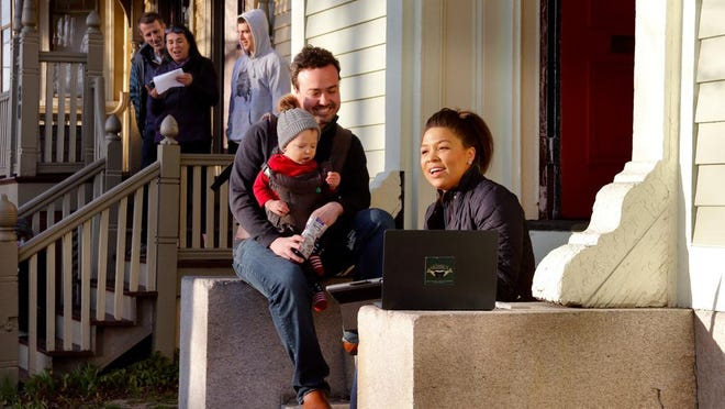 In March, Jenica Conley, right, with her husband Dylan Conley and baby Copeland, lead the neighborhood in the first of a nightly sing-a-long in their West Broadway neighborhood to relieve the monotony of coronavirus social distancing.