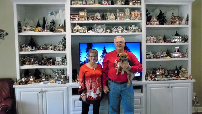 Marcia and Rick Gautier along with Nemo, welcome Christmas with their annual display of Snow Village collectibles. Directly above the Gautier's, the top two shelves tout the first pieces that started their collection.