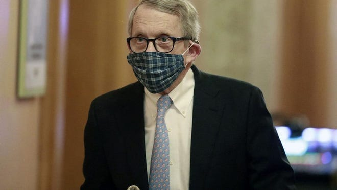Ohio Gov. Mike DeWine walks into a coronavirus news conference on April 16, 2020, at the Statehouse in Columbus wearing a mask his wife, Fran, made him.