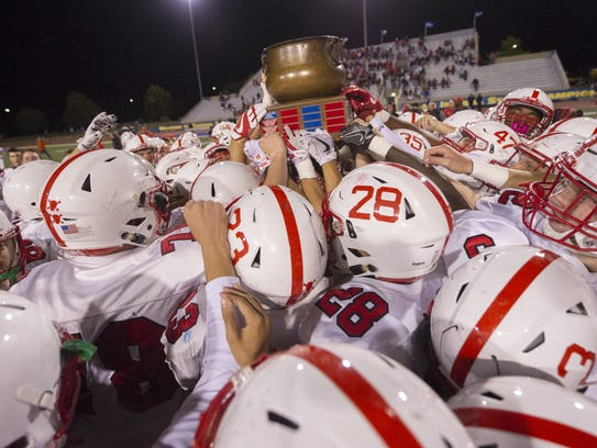 The Center Grove players celebrate with the trophy