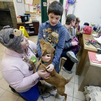 Amber Harrell, left, and her son, Donovan Heckner, play with Lady, while volunteer Kathy Paevk, right, helps Nancy Heckner and Michelle McGinnis fill out adoption papers at Chances Animal Rescue in Appleton on Wednesday. Nancy Heckner is adopting the lab mix. The center is scrambling to find homes for more than 100 cats and dogs before being evicted.