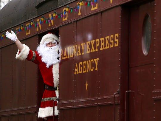 Santa (Jason Crawford) waves to families gathered as