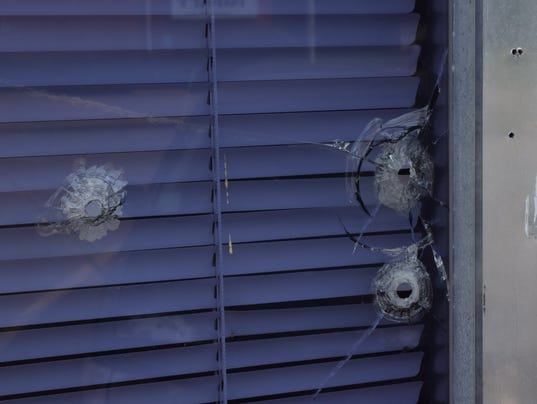 Wanda Gilmore, wife of the Rev. Charlie Gilmore, points to three bullet holes that were shot at the window of the United Educatiional Missionary Baptist Association.